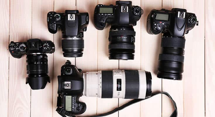 digital cameras on wooden table, top view