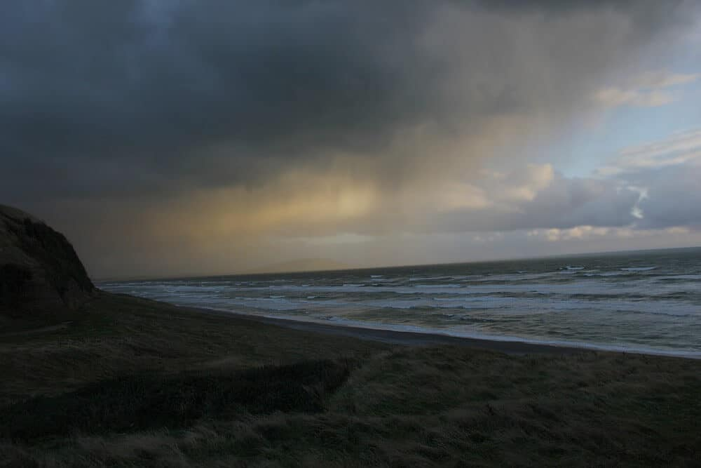 an underexposed image of the ocean and a storm coming in.