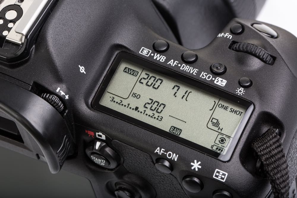 DSLR LCD with settings - shutter speed, aperture, ISO, AF mode.