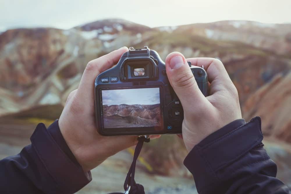 Landscape travel photographer hands holding camera and taking photo of mountains