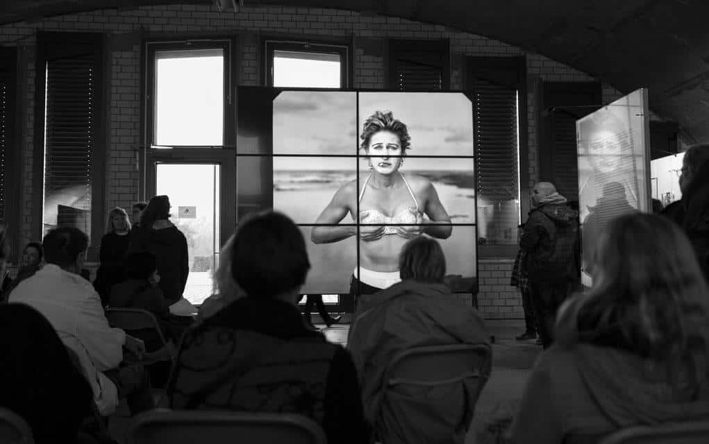 Black and white photo of a photography exhibit showcasing work by Annie Leibovitz.