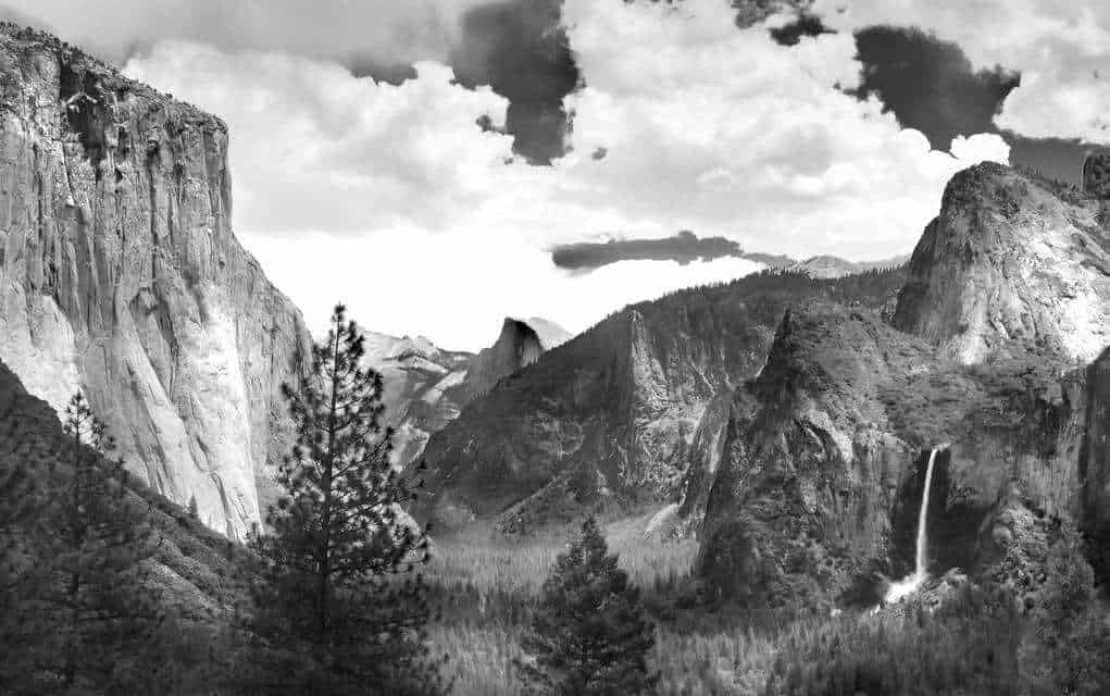 A black and white photograph of mountains photographed by Ansel Adams.
