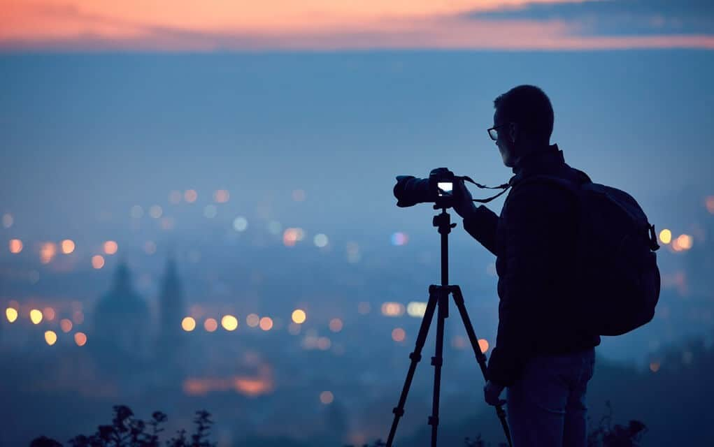 Silhouette of man taking photo on top of a mountain with his DSLR.