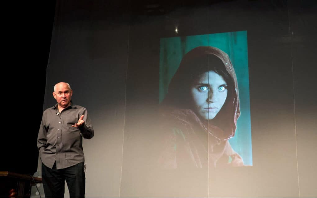 Photo of Steve McCurry presenting his photo exhibit with famous photo, Afghan Girl, in the background.