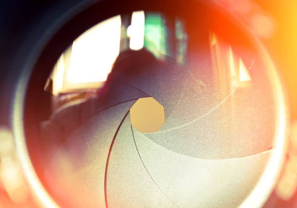 Close up of camera lens with aperture blades and bokeh in the background.